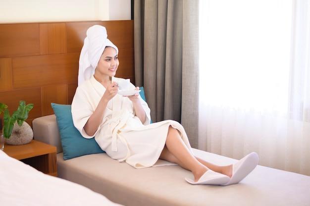 Une femme détendue portant un peignoir blanc et une serviette en prenant un café le matin