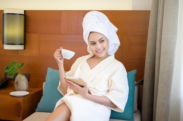 Une femme détendue portant un peignoir blanc et une serviette en prenant un café tout en utilisant la tablette le matin