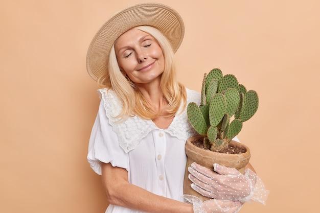 Une femme détendue et ravie aux cheveux blonds garde les yeux fermés tient un pot de cactus succulent vert épineux porte un chapeau robe blanche des gants en dentelle se sent satisfait obtient une plante d'intérieur comme présente isolée sur un mur beige