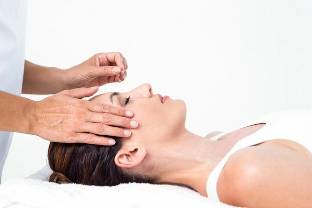 Femme détendue recevant un traitement d'acupuncture