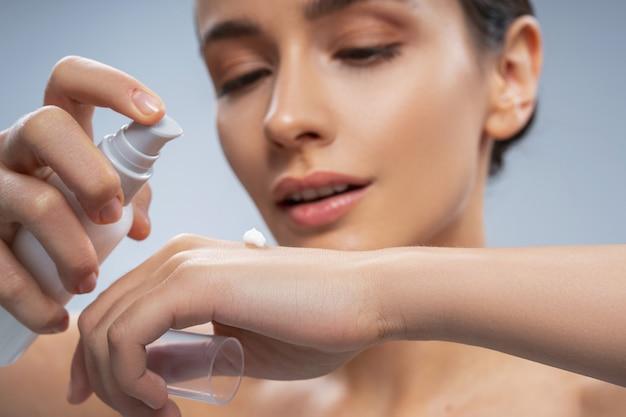 Femme détendue s'occupant de la peau des mains avec des cosmétiques