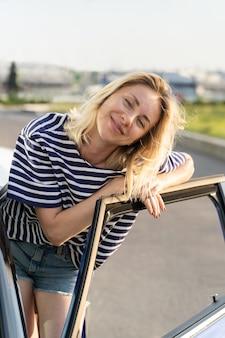 Une femme détendue se tient à la porte ouverte de la voiture au parking femme heureuse propriétaire du véhicule prête pour un voyage sur la route