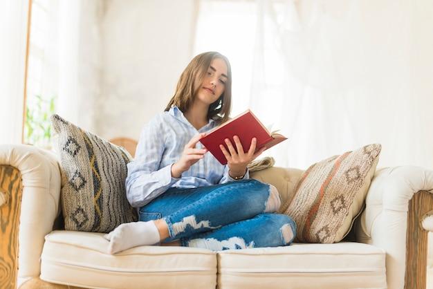 Femme de détente assis sur un canapé en train de lire un roman