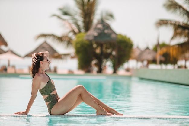 Femme détente au bord de la piscine dans un hôtel de luxe bénéficiant de vacances parfaites à la plage