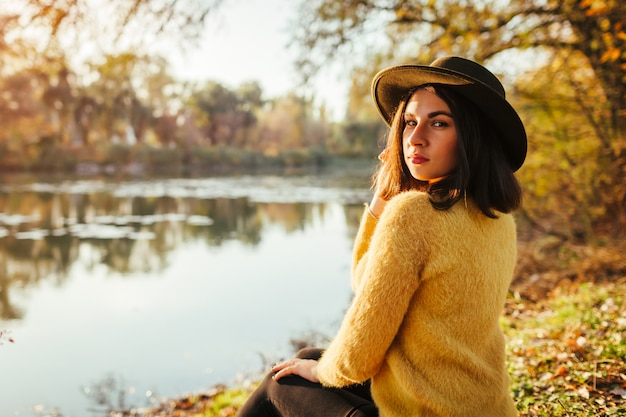 Femme de détente en automne rivière au coucher du soleil. fille élégante assise sur la banque et regardant la caméra