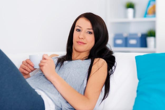 Femme de détente sur le canapé avec une tasse de café