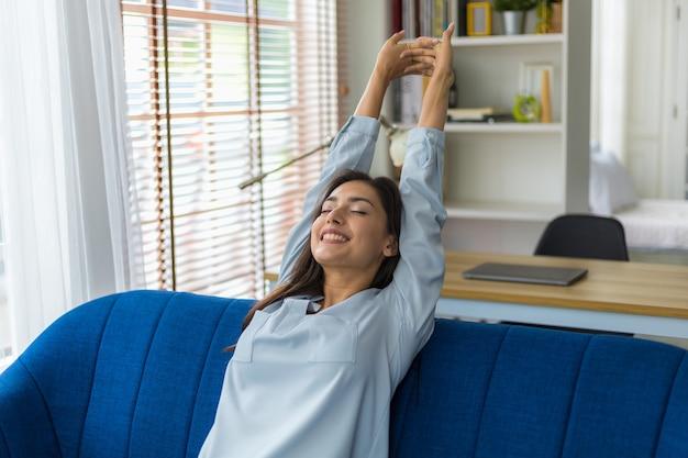 Femme détente sur canapé avec les yeux fermés et les mains derrière la tête à la maison