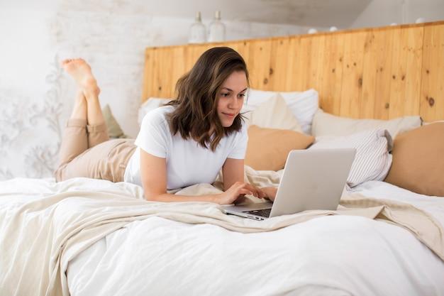 Femme de détente sur le lit à l'aide d'un ordinateur portable pour un appel vidéo en images k plat moderne de haute qualité