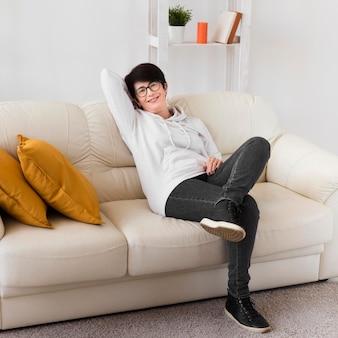 Femme de détente à la maison sur le canapé