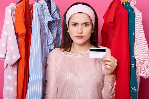 Une femme détenue détient une carte de crédit et semble stressée, elle a des problèmes financiers. une femme brune dépense tout l'argent de sa carte. le modèle pose contre des cintres avec des robes colorées. concept de magasinage.