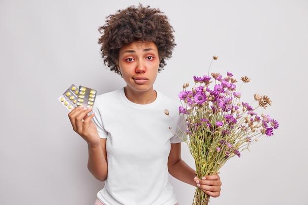Femme détient des médicaments sur l'allergie détient bouquet de fleurs sauvages se soucie de la santé a l'air malheureux malade isolated over white