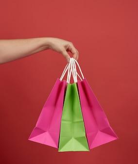 Femme détient pile de sacs en papier sur fond rouge, concept commercial, gros plan