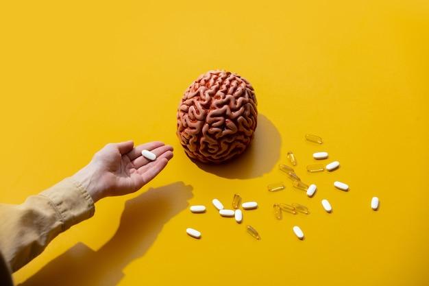 Femme détient des pilules près du cerveau sur une surface jaune