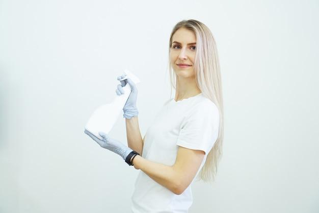 Femme détient un vaporisateur avec un antiseptique ou un détergent comme des pistolets santé ou concept de nettoyage covid sur fond blanc