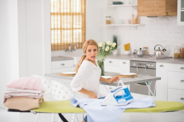 Femme en détresse assise à demi-tour à table qui a vu le fer chaud oublié sur la chemise