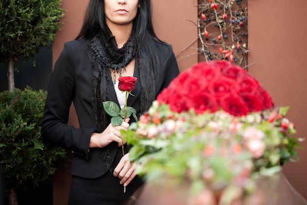 Femme en deuil lors de funérailles avec cercueil