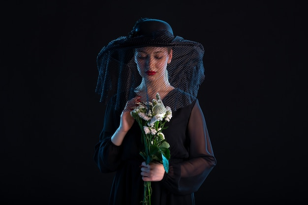 Femme en deuil vêtue de noir avec des fleurs sur une surface noire isolée mort funéraire