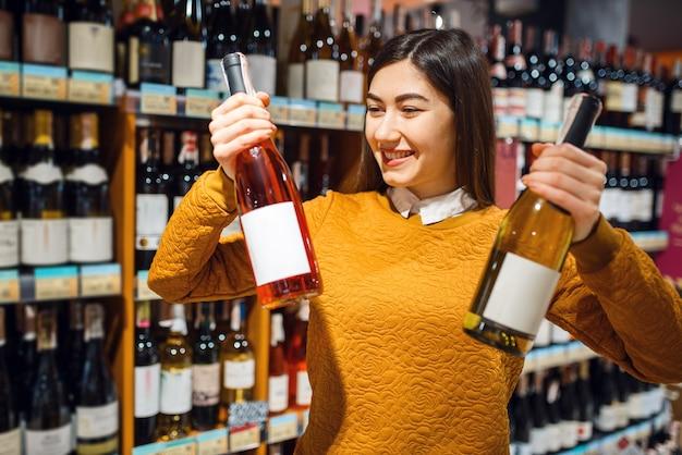 Femme avec deux bouteilles d'alcool en épicerie