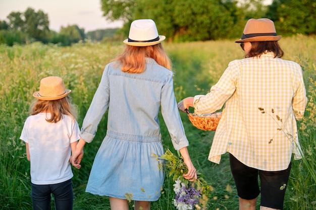 Femme avec deux filles marchant dans un pré avec un panier d'oeufs, vue arrière, heure d'or