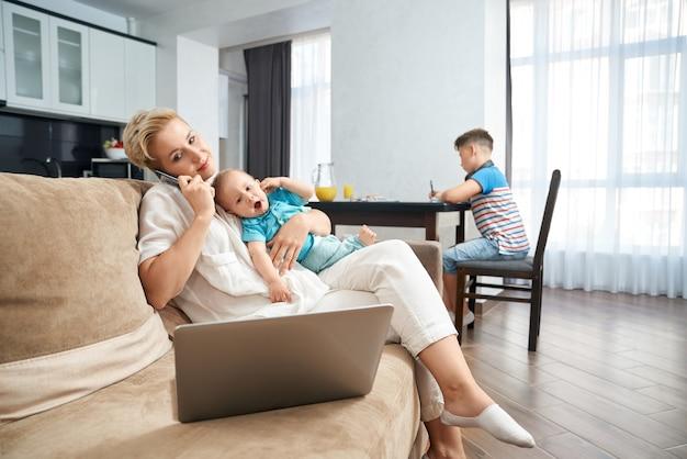 Femme avec deux fils travaillant à la maison