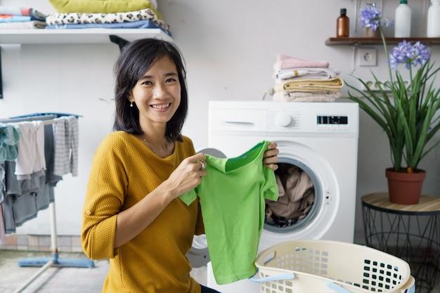 Femme devant la machine à laver souriant à la caméra tout en faisant du linge à l'intérieur de chargement de vêtements