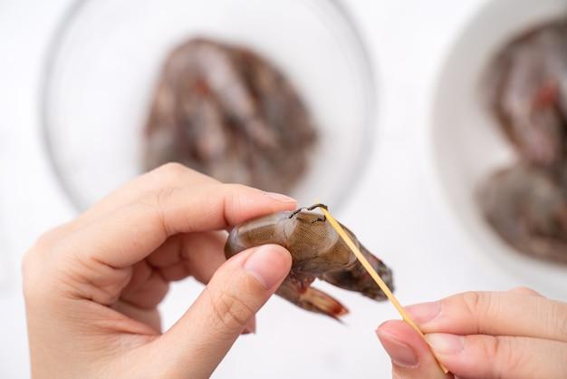 La femme déveine les crevettes et tire la ligne du tractus intestinal lors de la cuisson des crevettes.