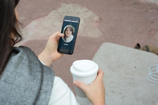 Femme déverrouillant un smartphone avec technologie de reconnaissance faciale