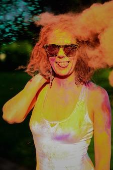 Femme dhead re s'amusant dans un nuage de peinture sèche orange au festival des couleurs holi