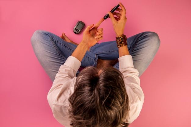 Femme diabétique assise sur le sol à l'aide d'appareils pour mesurer la glycémie.