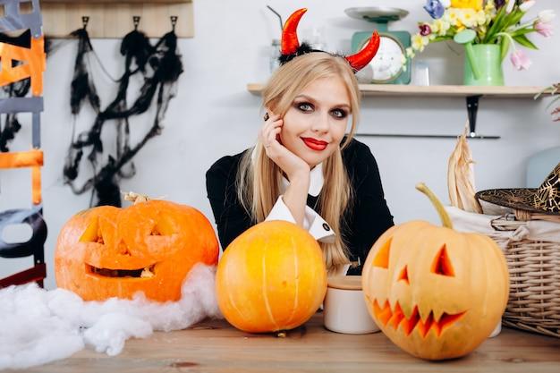 Femme diable assis à la table à côté d'une citrouilles et souriant en regardant la caméra