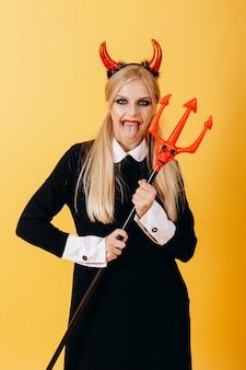 Femme diable debout contre un jaune et montrant la langue. verticale