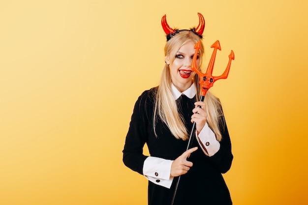Femme diable debout contre un jaune et montrant la langue