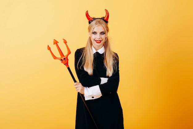 Femme diable debout contre un jaune
