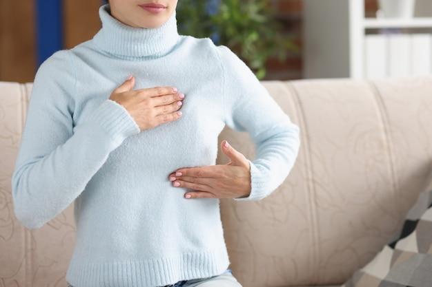 Une femme diagnostique elle-même les glandes mammaires. concept de formation de masse mammaire