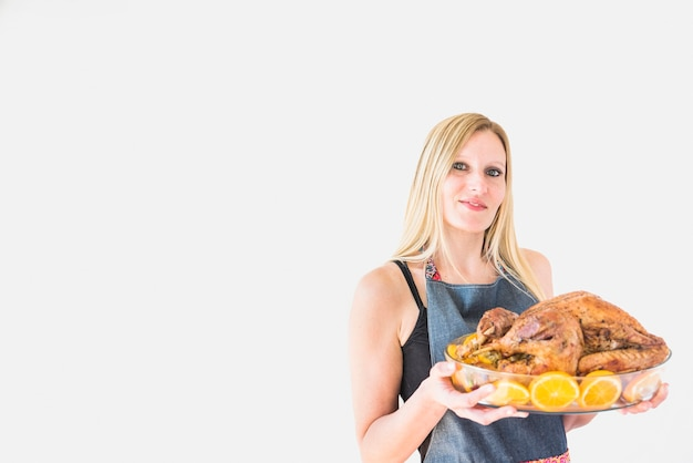 Femme avec dinde au four en verrerie