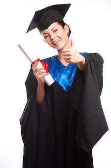 Une femme avec un diplôme en main alors qu'elle regarde la caméra