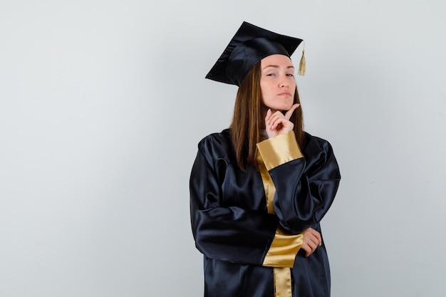 Femme diplômée étayant le menton sur le doigt en robe académique et à la fierté, vue de face.