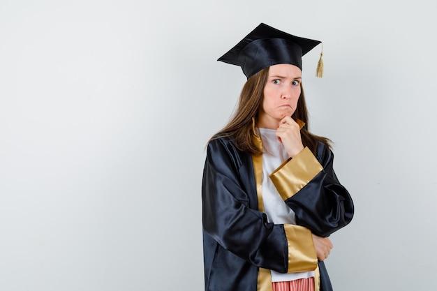 Femme diplômée étayant le menton sur place en robe académique et à la vue pensive, avant