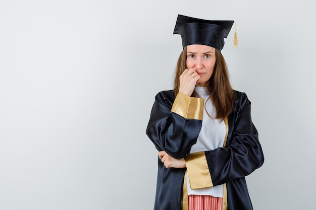 Femme diplômée en gardant la main sur le menton dans des vêtements décontractés, uniforme et regardant anxieux, vue de face.