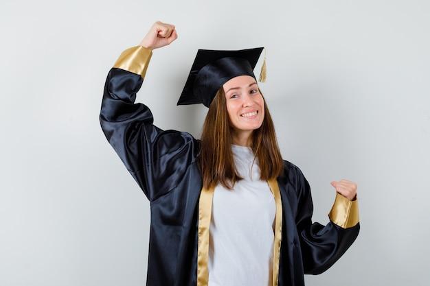 Femme diplômée montrant le geste du gagnant dans des vêtements décontractés, uniforme et à la recherche de bonheur. vue de face.