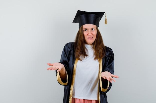 Femme diplômée montrant un geste impuissant dans des vêtements décontractés, uniforme et à la confusion, vue de face.
