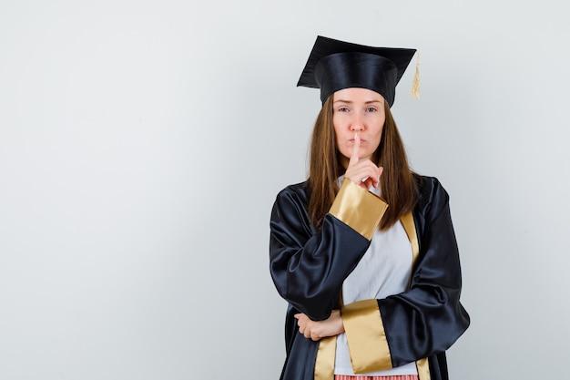 Femme diplômée montrant le geste de silence en uniforme, vêtements décontractés et à la vue sensible, de face.