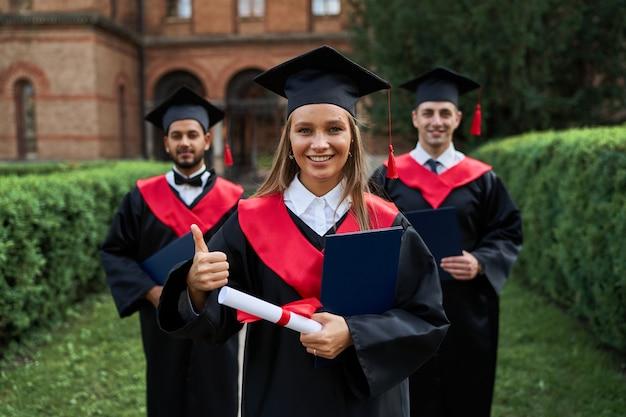 Une femme diplômée montre comme avec ses amis en robes de graduation titulaires d'un diplôme et souriant à la caméra.