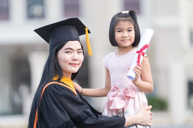 Femme diplômée avec petite fille le jour de sa remise des diplômes