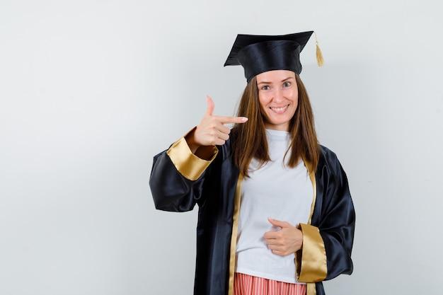Femme diplômée pointant à droite dans des vêtements décontractés, uniforme et à la recherche de bonheur. vue de face.