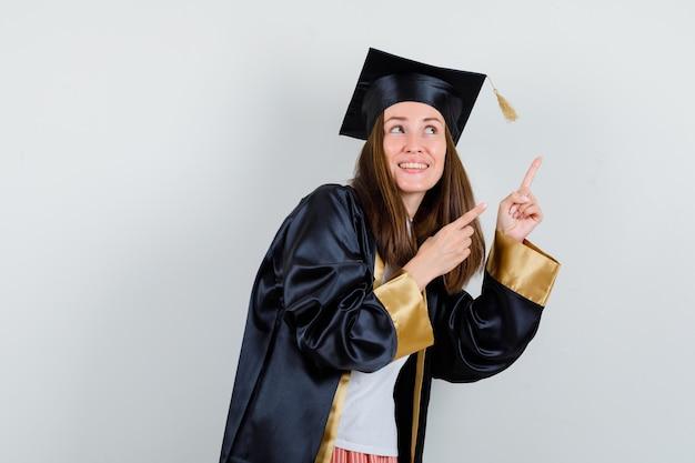 Femme diplômée pointant vers le haut dans des vêtements décontractés, uniforme et à la joyeuse, vue de face.