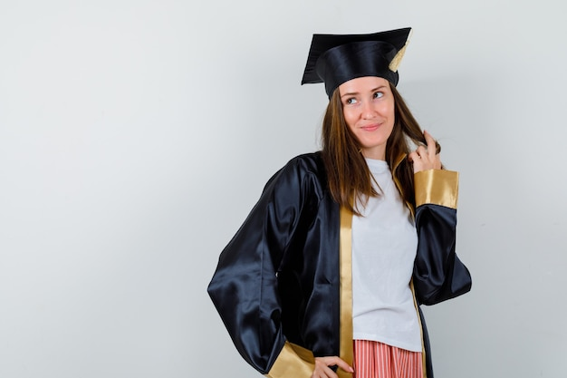 Femme diplômée posant tout en tenant son brin en uniforme, vêtements décontractés et à la rêveuse, vue de face.