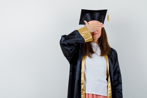 Femme diplômée tenant la main sur les yeux dans des vêtements décontractés, uniforme et à la recherche d'espoir. vue de face.