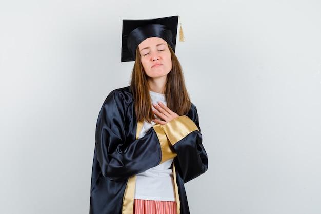 Femme diplômée tenant les mains sur la poitrine dans des vêtements décontractés, uniforme et à la recherche d'espoir. vue de face.