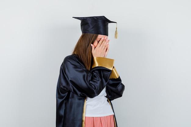 Femme diplômée en uniforme, vêtements décontractés couvrant le visage avec les mains et regardant déprimé, vue de face.